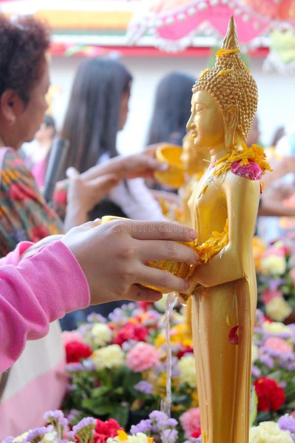 Bevattna att hälla till Buddhastatyn i Songkran festivaltradition fotografering för bildbyråer