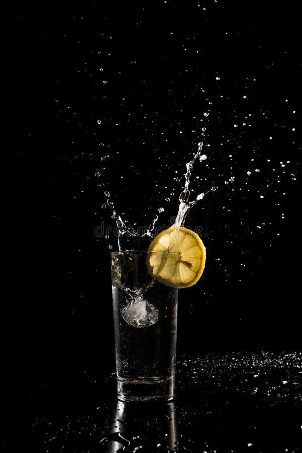 Bevattna att plaska ut ur ett exponeringsglas, som en iskub tappas in till a royaltyfri foto