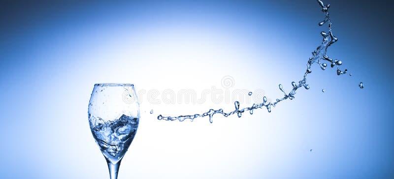Bevattna att plaska ut ur fallande exponeringsglas på blå bakgrund med snuten royaltyfria foton