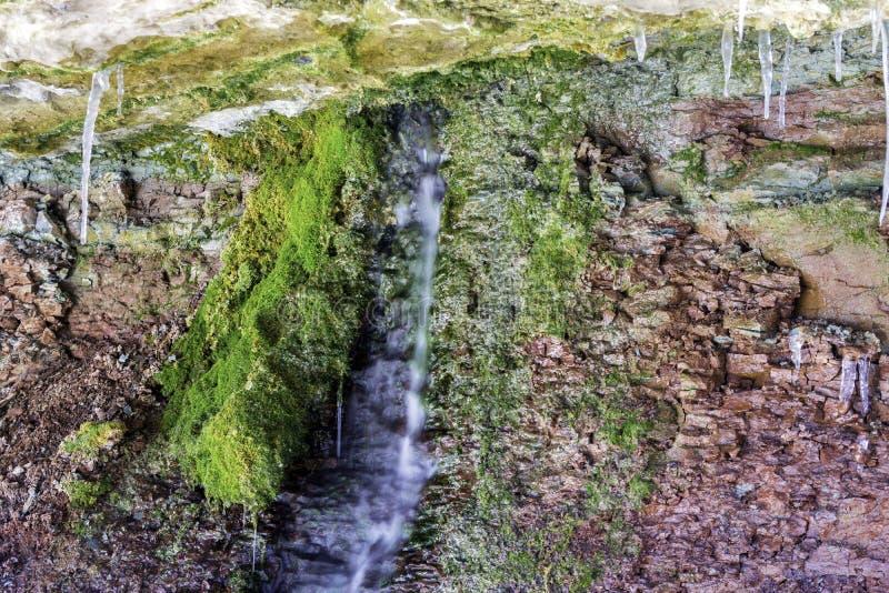 Bevattna att sippra från rött vaggar framsidan under överhäng, grön mossa gr arkivbild