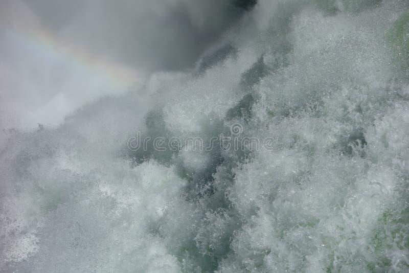 Bevattna att skumma från en vattenfall med en svag regnbåge arkivbilder