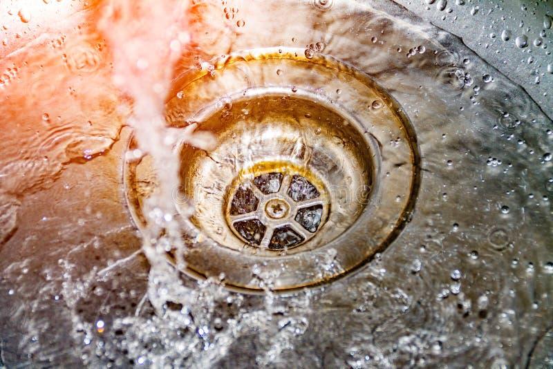 Bevattna avrinningar in i vasken, vask, och rinnande vatten för bakgrunden, tar omsorg av vattnet royaltyfria foton