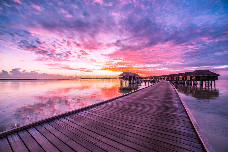 Bevattna bungalower med härlig det skymninghimmel och havet i Maldiverna exponering long arkivfoton
