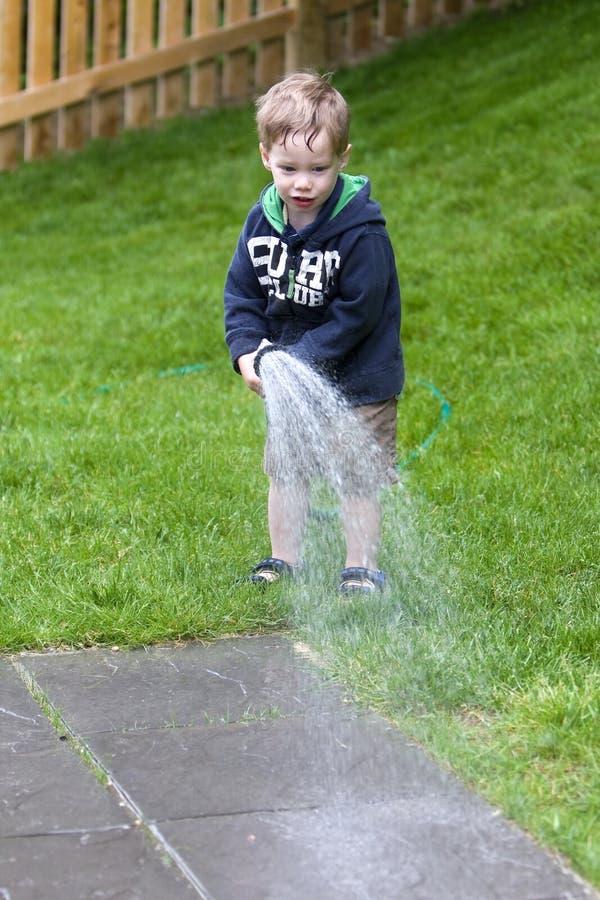 bevattna för pojketrädgård royaltyfri bild