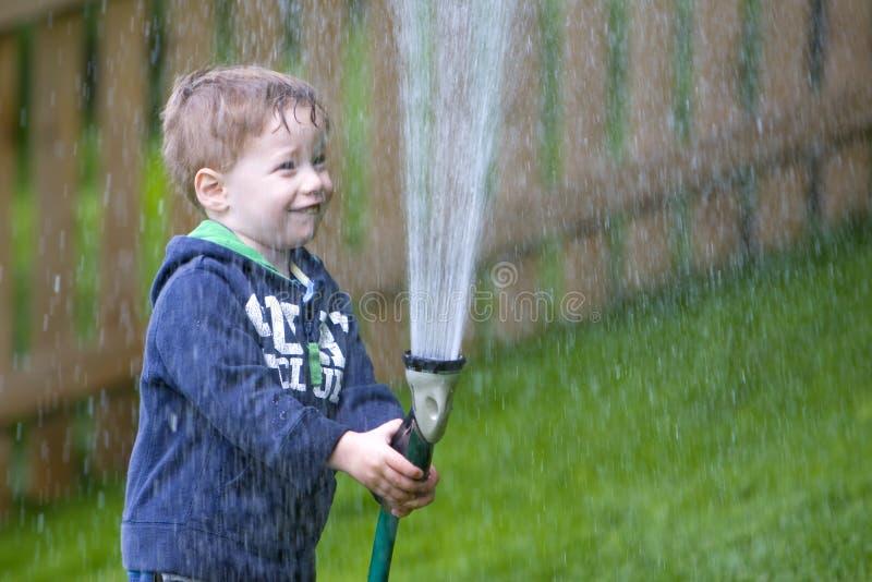 bevattna för pojketrädgård arkivbild
