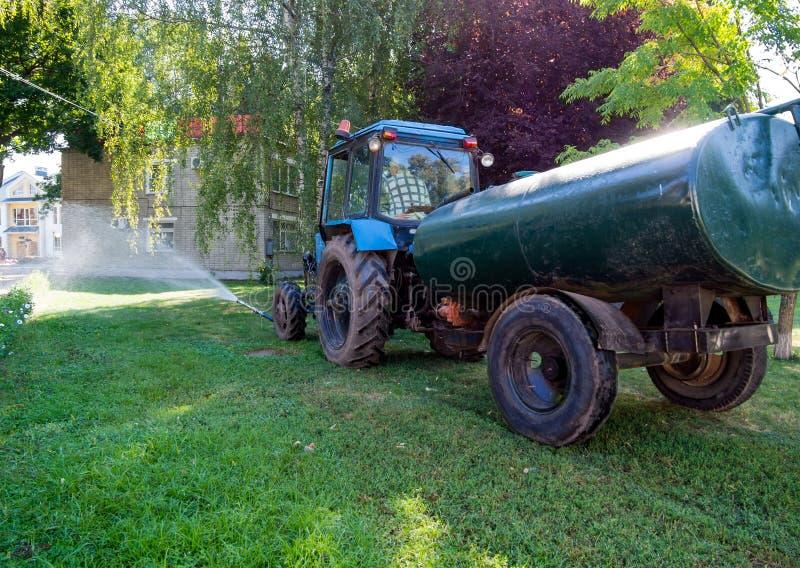 Bevattna gräsmattan genom att använda traktoren 'Vitryssland ', royaltyfri fotografi