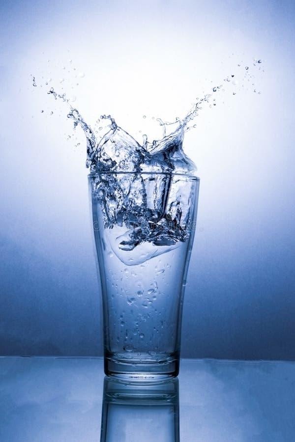 Bevattna i exponeringsglas med bevattnar färgstänk royaltyfri foto
