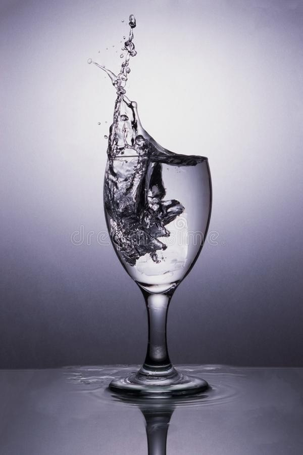 Bevattna i exponeringsglas med bevattnar färgstänk royaltyfri fotografi