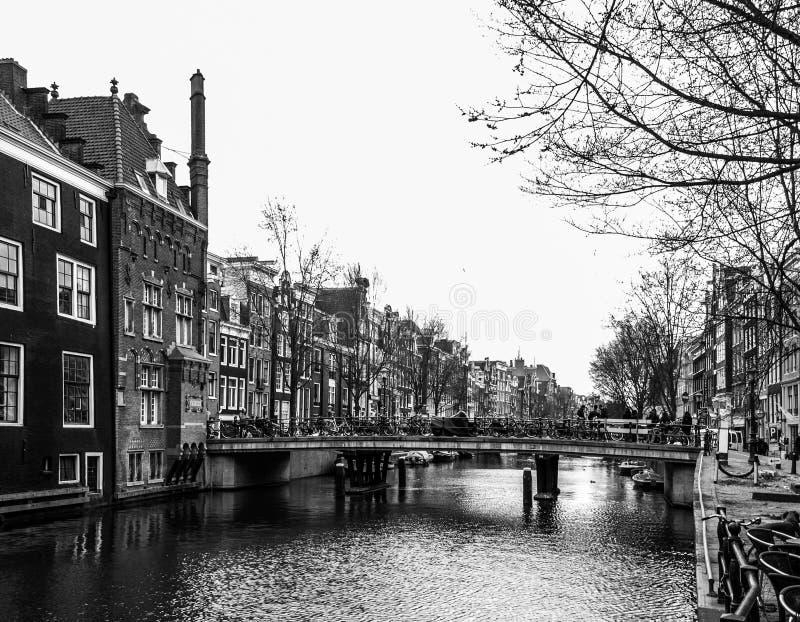Bevattna kanalen, aka gracht och begränsa hus längs den i Amsterdam stadsmitt, Nederländerna, svartvit bild arkivfoto