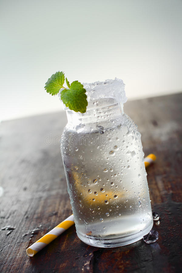Bevattna kruset med en liten växt och ett sugrör arkivfoto