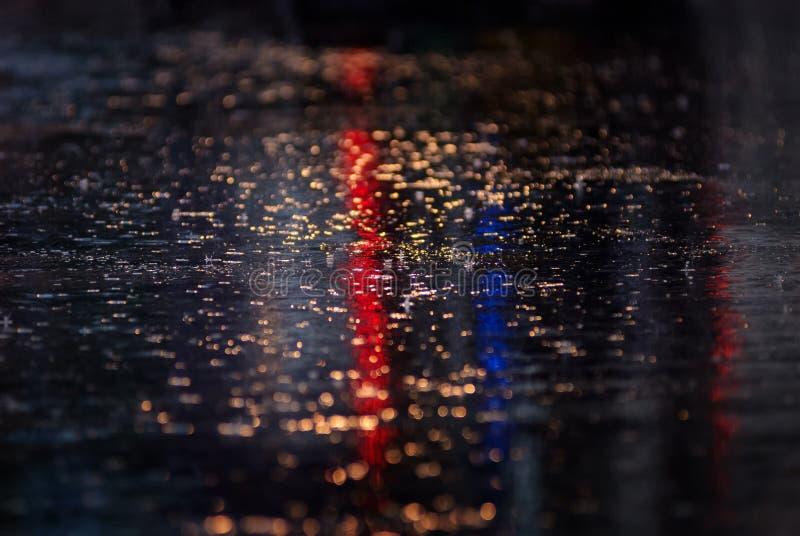 Bevattna reflexionen på vägen med färgrik trafikljus arkivbild
