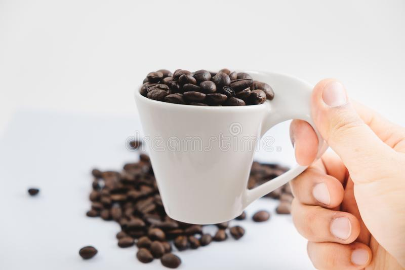 beverage background hand of woman hold cup with coffee bean place on white table with copy space. image for isolated, drink, food stock photos