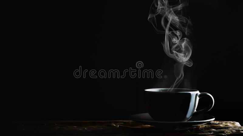 Beverage background of hot coffee, tea or chocolate in black cup on wooden plank in dark background royalty free stock image