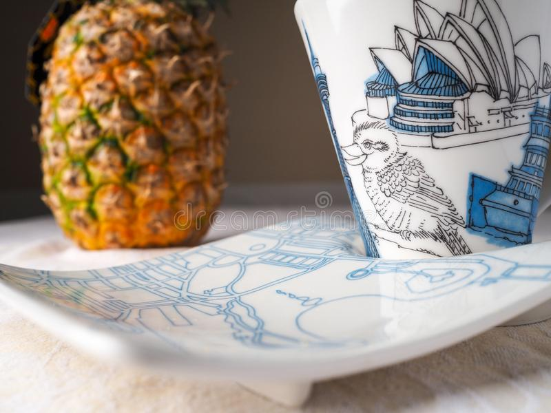 Beverage on a blue cup and pineapple on the bBackground royalty free stock photography