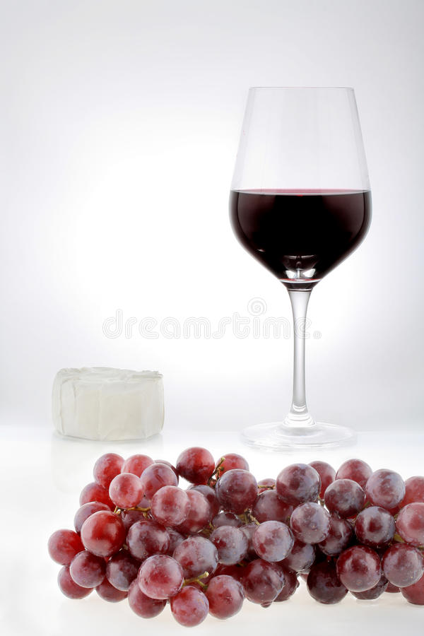 Beverage red wine. Wineglass with grapes and Camenbert cheese royalty free stock images