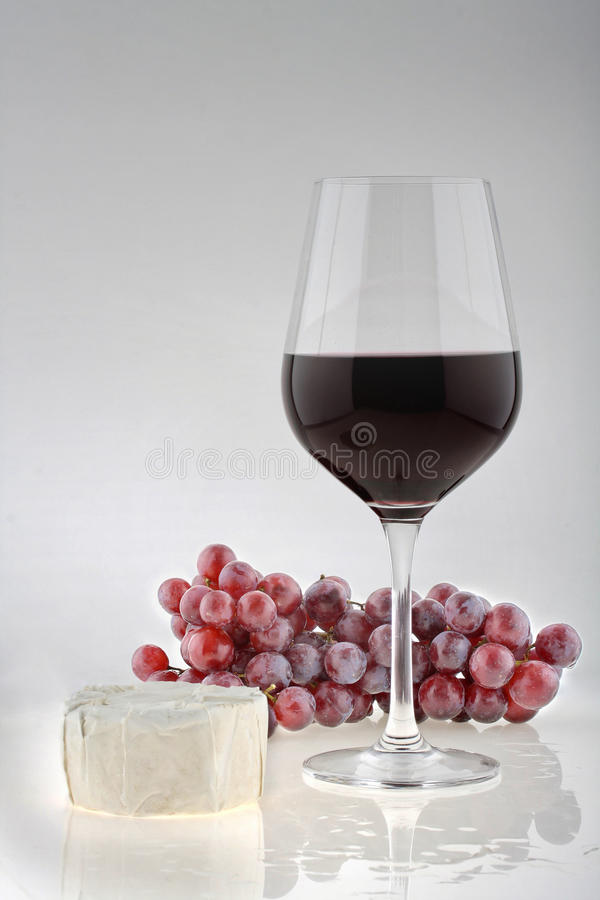 Beverage red wine. Wineglass with grapes and Camenbert cheese stock image