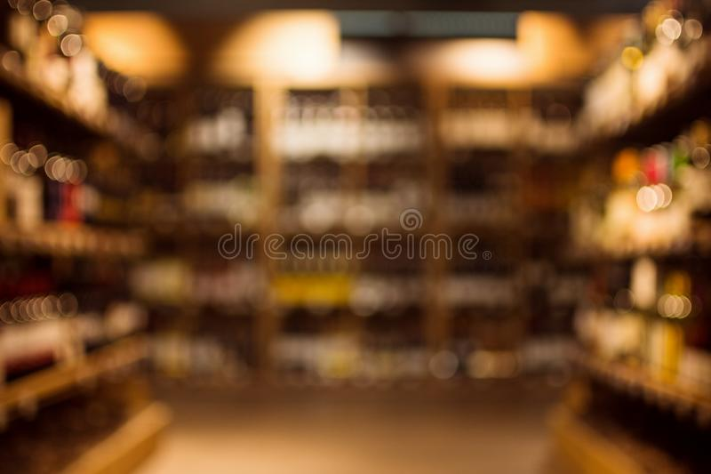 Beverages in drink store. Different beverages are on shelves in illuminated drink store, blurred or defocused background stock images