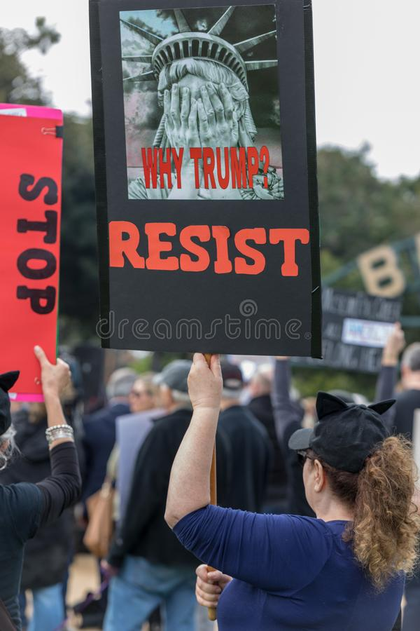 Why Trump? RESIST sign held by protesters. BEVERLY HILLS, CALIFORNIA - MARCH 12, 2018: A protester holds a sign that reads, `Why Trump? RESIST` at the Defend stock photography