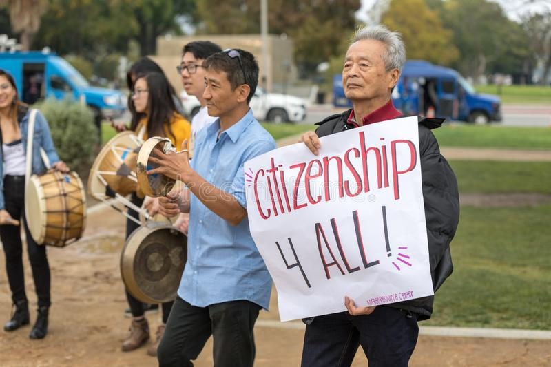 Citizenship 4 All sign held by older Korean male. BEVERLY HILLS, CALIFORNIA - MARCH 12, 2018: A protester with the Korean Resource Center holds a sign that reads stock images