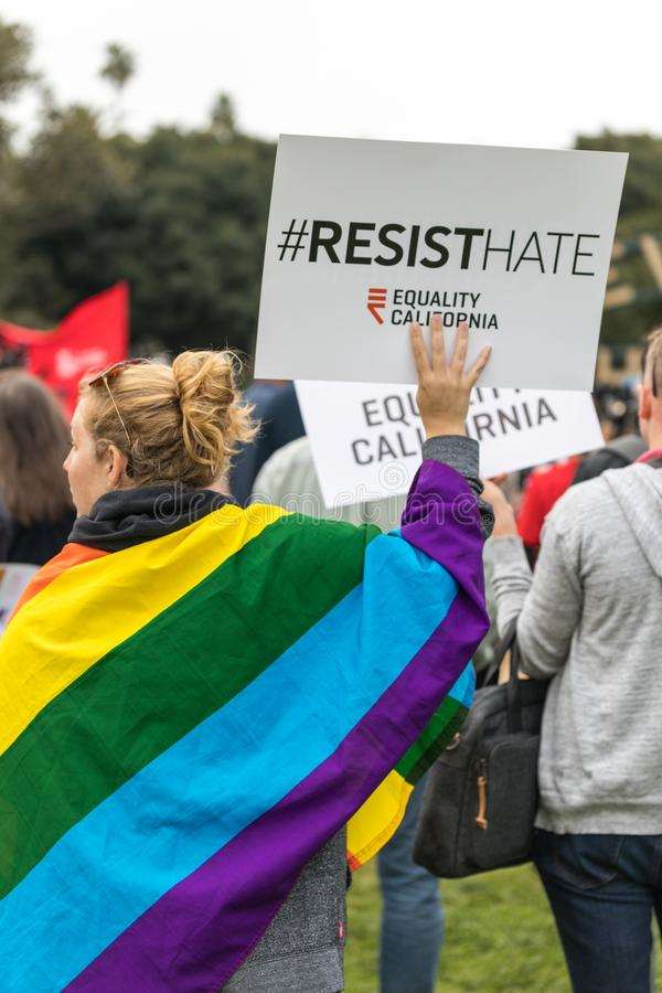 Resist Hate sign and the Rainbow Flag. BEVERLY HILLS, CALIFORNIA - MARCH 12, 2018: A protester with the Rainbow flag drapper over her holds a sign that reads, ` stock photos