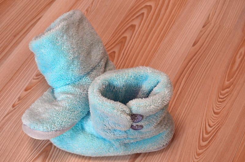 Bevinden de pluche warme blauwe pantoffels zich op een houten parketvloer in de ruimte De winter het koelen, verwarmend, koud hui stock foto's