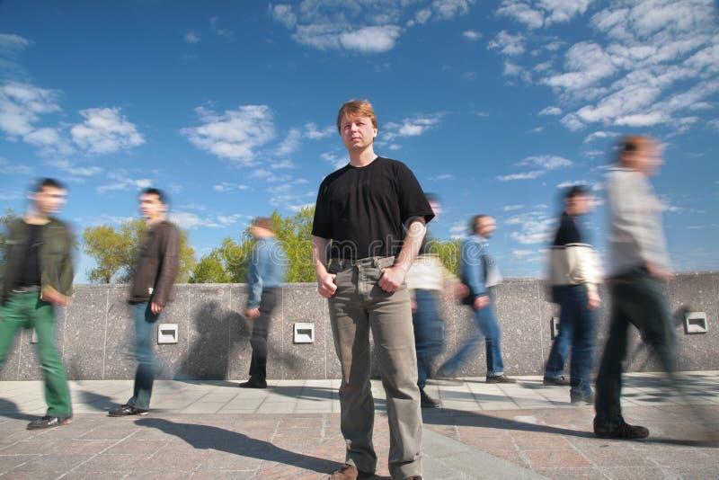 Bevindende mens onder bewegende voetgangers royalty-vrije stock foto