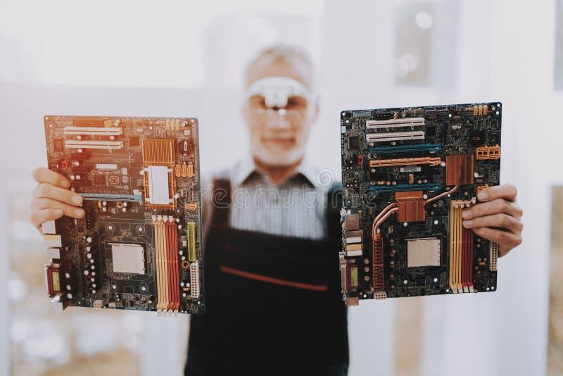 Bevindende Oude Arbeider met Motherboards in Handen stock afbeeldingen