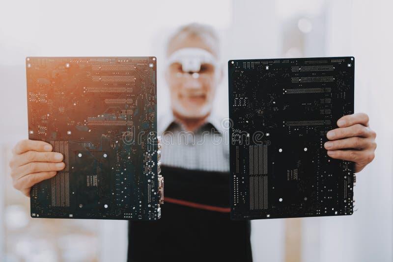 Bevindende Oude Arbeider met Motherboards in Handen stock afbeelding
