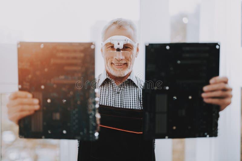 Bevindende Oude Arbeider met Motherboards in Handen royalty-vrije stock afbeelding