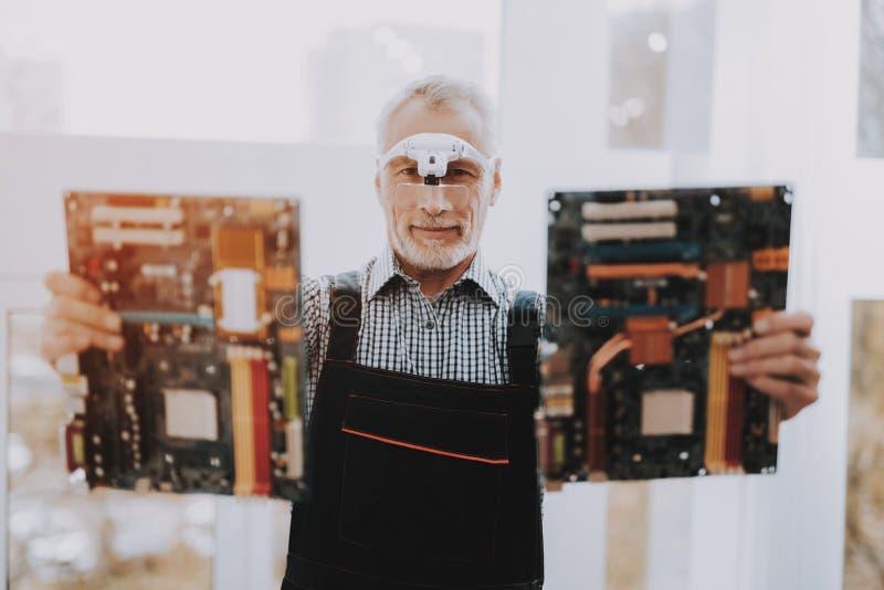 Bevindende Oude Arbeider met Motherboards in Handen royalty-vrije stock afbeeldingen