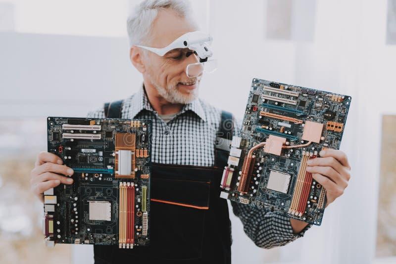 Bevindende Oude Arbeider met Motherboards in Handen stock foto