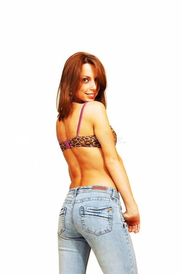 Bevindende vrouw in jeans en bustehouder. stock afbeelding