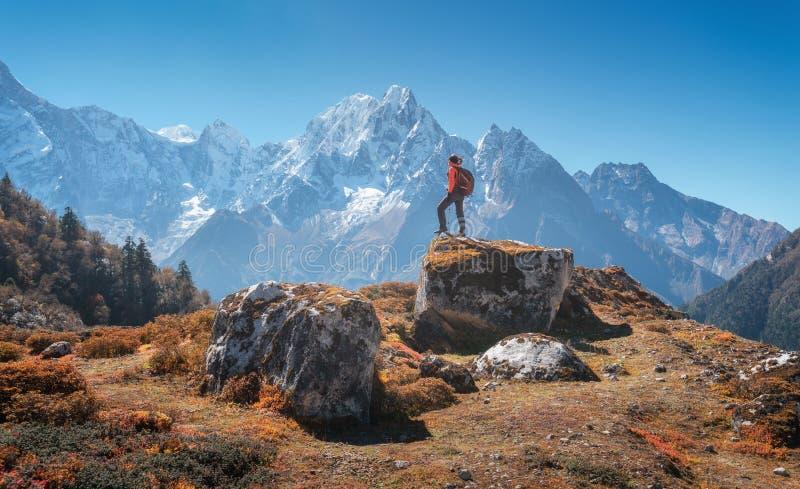 Bevindende vrouw met rugzak op de steen en de mooie berg stock afbeeldingen