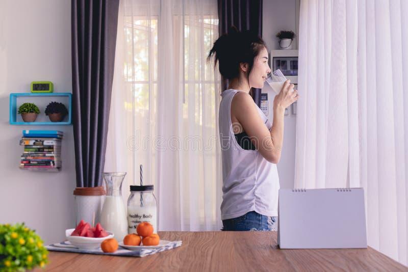 Bevindende vrouwenconsumptiemelk in woonkamer thuis stock foto