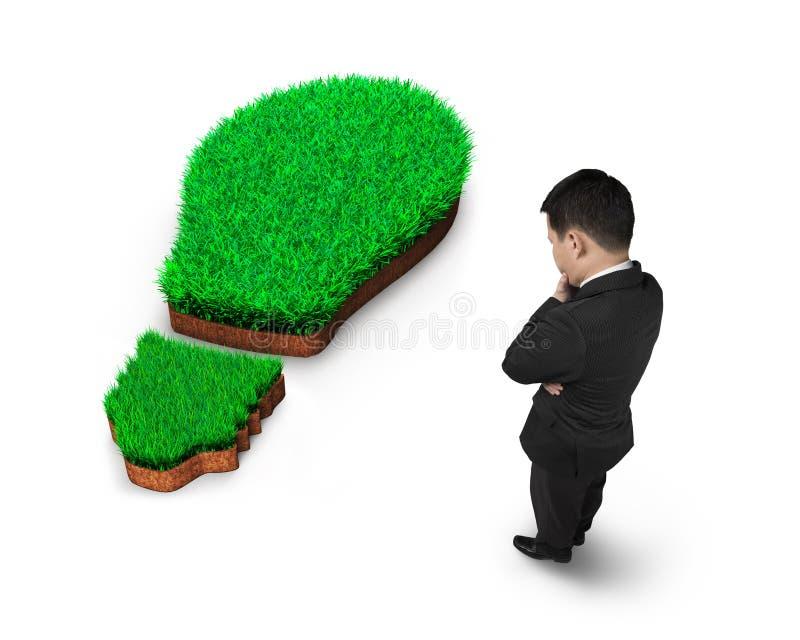Bevindende zakenman die over groen gras van gloeilamp nadenken stock afbeelding