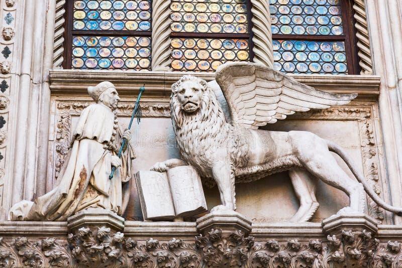 Bevingat lejon och en präst Detail av slotten Palazzo Ducale för doge` s i Venedig, Italien arkivbilder