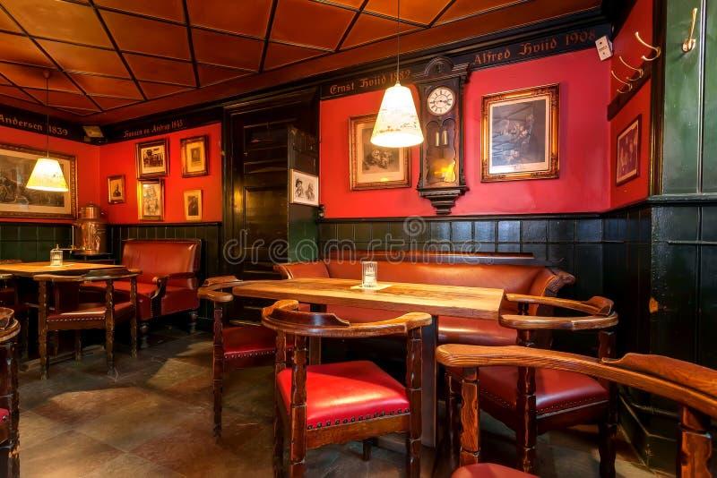 Bevitori aspettanti interni della barra accogliente dentro stanza d'annata con le tavole e le sedie classiche di stile fotografia stock