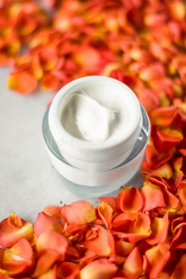 Bevochtigende de room en de bloembloemblaadjes van het schoonheidsgezicht op marmer, luxecosmetische product stock fotografie