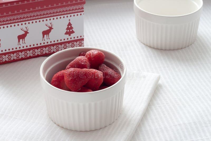 Bevroren aardbeien in een witte plaat op een wit tafelkleed op de achtergrond van Kerstmisdoos royalty-vrije stock foto's
