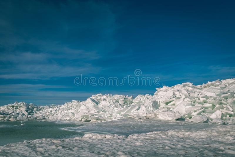 bevroren die meer met stapel van ijsijsschollen en blauwe hemel wordt behandeld - vinta stock fotografie