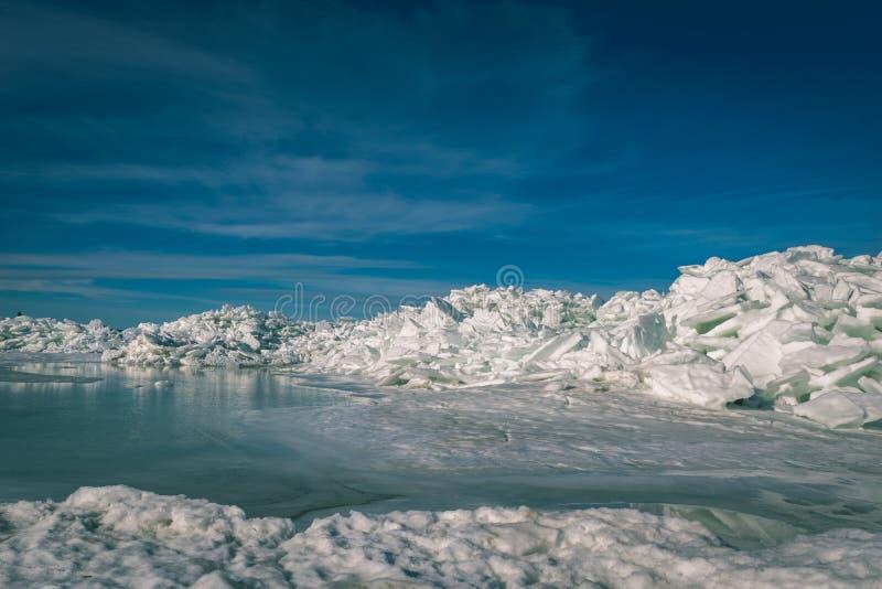 bevroren die meer met stapel van ijsijsschollen en blauwe hemel wordt behandeld - vinta stock afbeelding