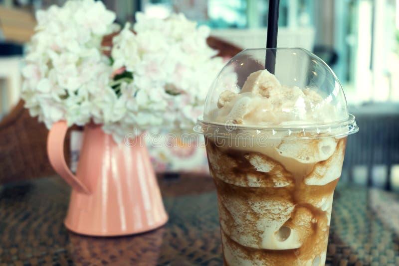 Bevroren frappe koffie in plastic mok gezet op de lijst van het rotanweefsel royalty-vrije stock afbeelding