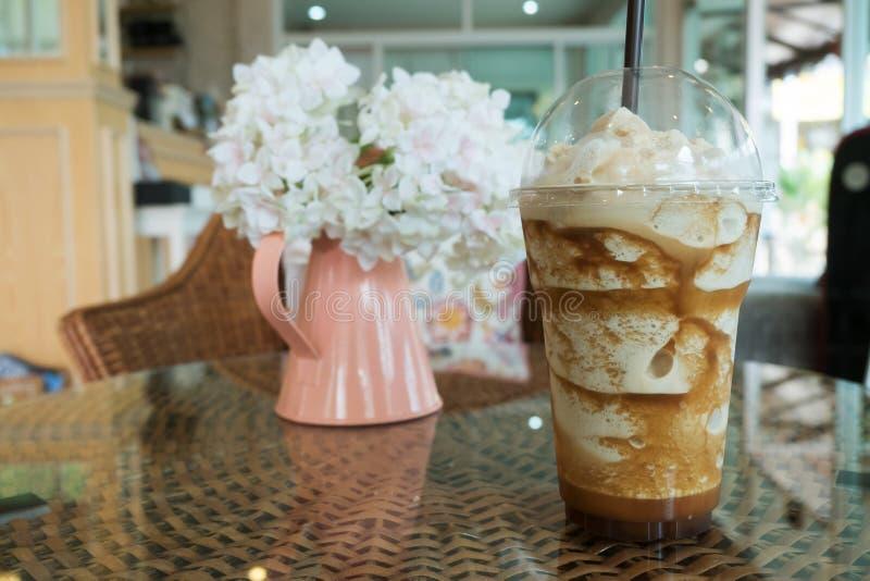 Bevroren frappe koffie in plastic mok gezet op de lijst van het rotanweefsel stock afbeelding