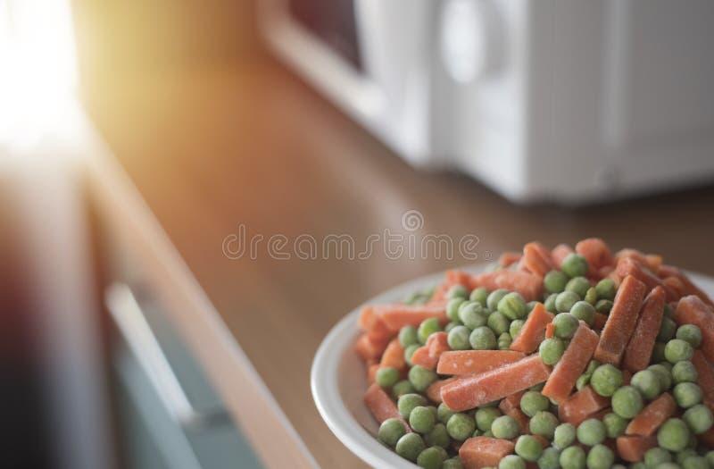 Bevroren groenten op witte plat dichtbij microgolf in keuken, cooki royalty-vrije stock afbeelding