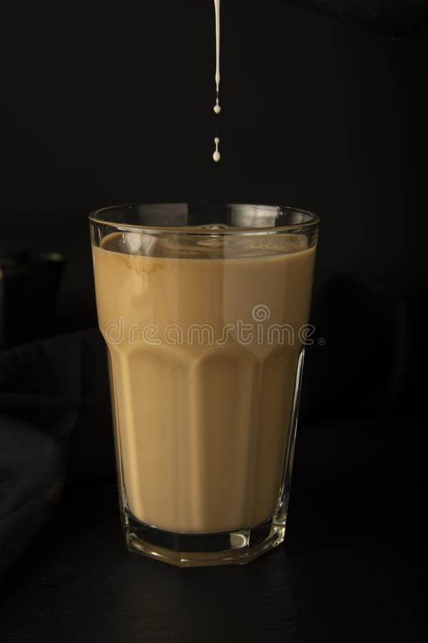 Bevroren koffie die in een lang glas met ijs worden gegoten Gietende melk in glas koffie Koude, het verfrissen zich, cafeïnemilks stock foto