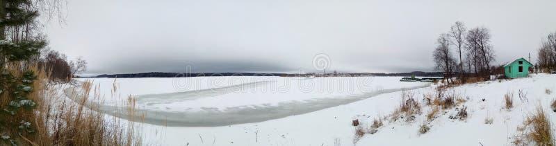 Bevroren meer in de sneeuw Rond het de winterbos, bomen Grijze ijzige hemel Banner Achtergrondbehang royalty-vrije stock afbeelding