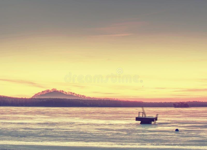 Bevroren meer in de winter Het Landschap van het de wintermeer met oranje zon stock afbeeldingen