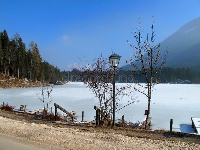 Bevroren meer in de winter met de Alpiene berg en de blauwe hemel royalty-vrije stock foto