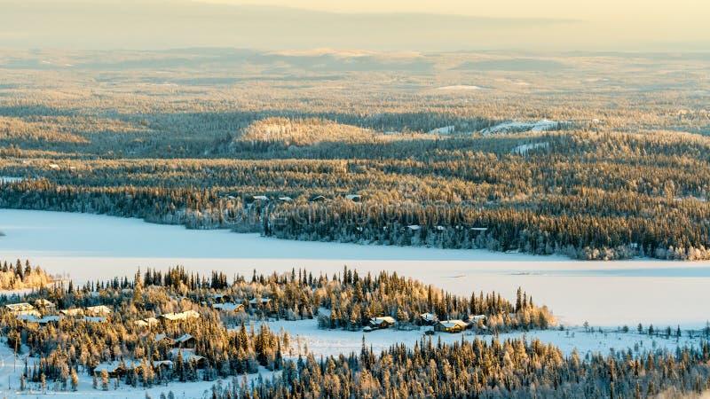 Bevroren meer en net bos in de winter Finland, Ruka stock foto's