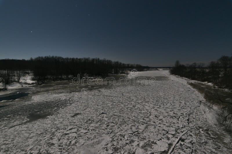 Bevroren rivier onder maanlicht stock fotografie